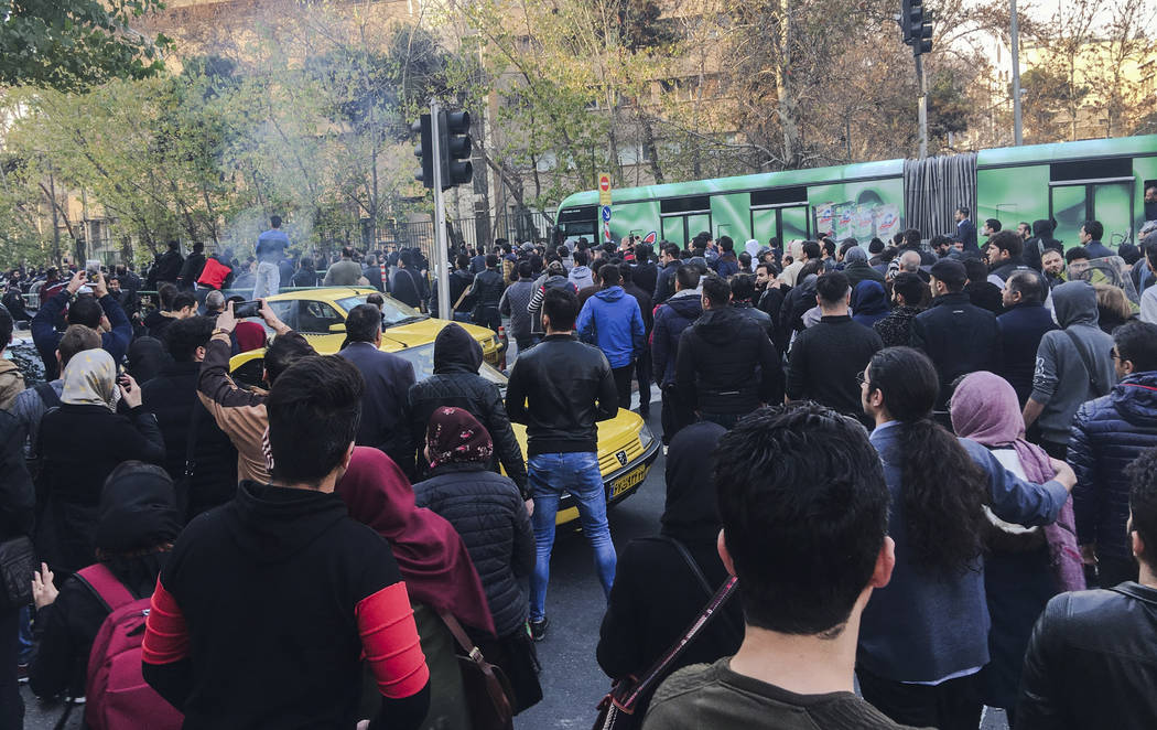 This photo taken by an individual not employed by the Associated Press and obtained by the AP outside Iran, demonstrators attend a protest over Iran's weak economy, in Tehran, Iran, Saturday, Dec. ...