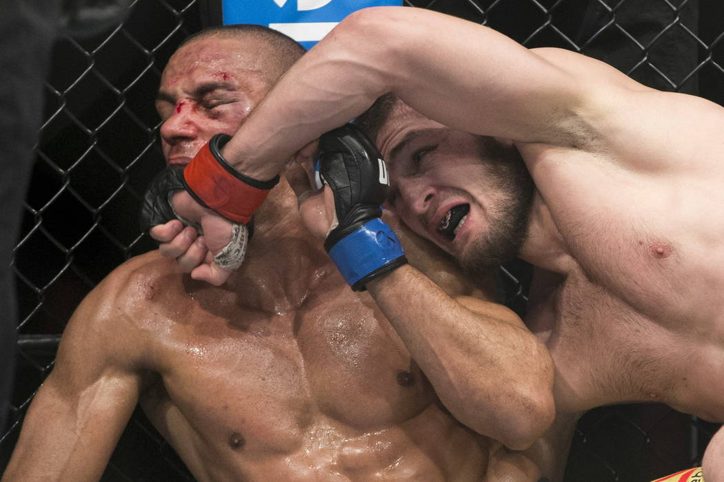 Edson Barboza, left, takes punches from Khabib Nurmagomedov in the UFC 219 lightweight bout at T-Mobile Arena in Las Vegas, Saturday, Dec. 30, 2017. Nurmagomedov won by unanimous decision. Erik Ve ...