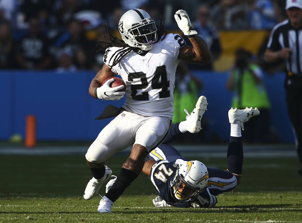 Oakland Raiders running back Marshawn Lynch, left, runs the ball past Los Angeles Chargers cornerback Trevor Williams (24) during an NFL game at StubHub Center in Carson, Calif. on Sunday, Dec. 31 ...