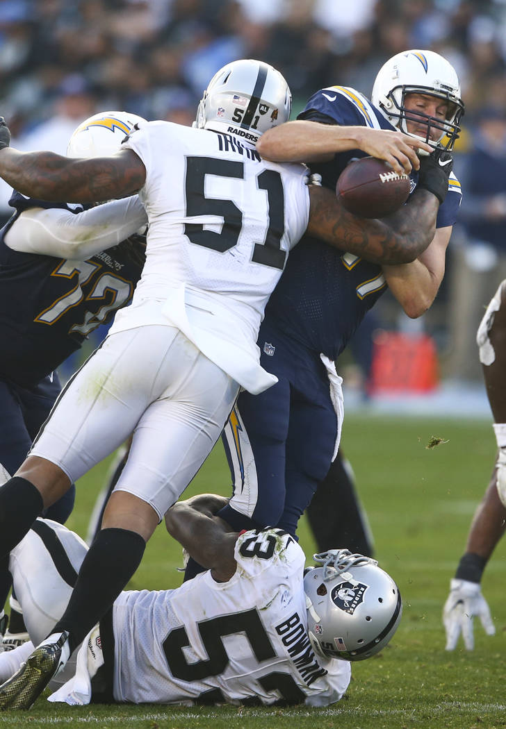 Los Angeles Chargers quarterback Philip Rivers (17) gets sacked by Oakland Raiders middle linebacker NaVorro Bowman (53) and Oakland Raiders outside linebacker Bruce Irvin (51) during an NFL game  ...