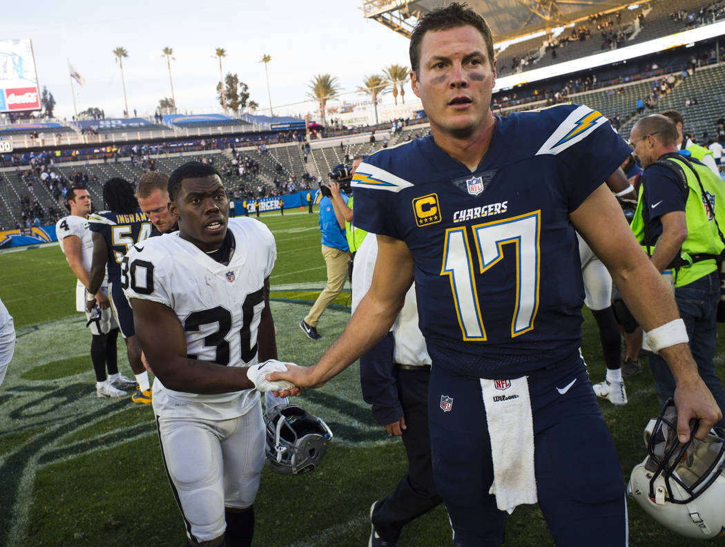 Oakland Raiders running back Jalen Richard (30) greets Los Angeles Chargers quarterback Philip Rivers (17) after an NFL game at StubHub Center in Carson, Calif. on Sunday, Dec. 31, 2017. Chase Ste ...