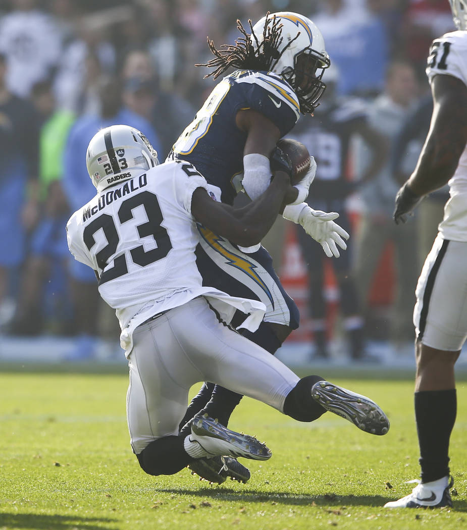 Oakland Raiders cornerback Dexter McDonald (23) takes down Los Angeles Chargers running back Melvin Gordon (28) during an NFL game at StubHub Center in Carson, Calif. on Sunday, Dec. 31, 2017. Cha ...