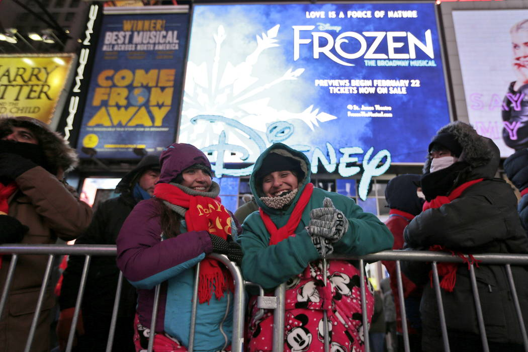 People waiting for midnight try to keep warm in Times Square as they gather to celebrate New Year's Eve, Sunday, Dec. 31, 2017, in New York. (AP Photo/Seth Wenig)