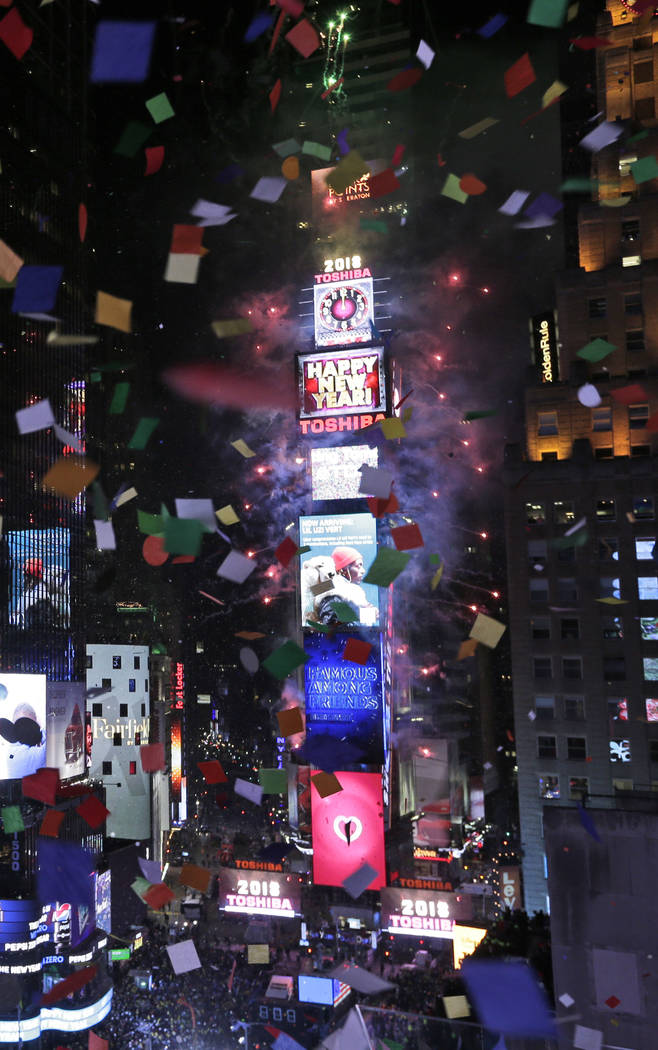 Fireworks erupt and confetti flies as the clock strikes midnight during the New Year's celebration in Times Square as seen from the Marriott Marquis in New York, Monday, Jan. 1, 2018. (AP Photo/Se ...