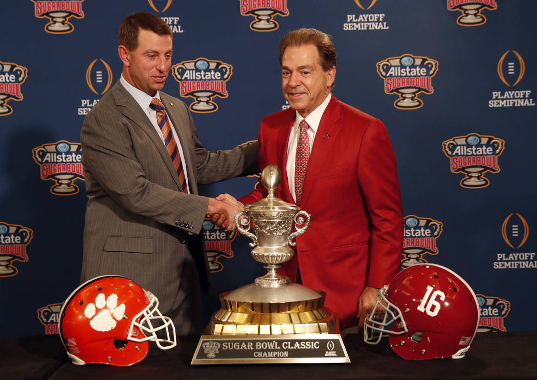 Clemson head coach Dabo Swinney and Alabama head coach Nick Saban, left, pose with the Sugar Bowl trophy for their upcoming semi-final playoff game, for the NCAA football national championship, in ...