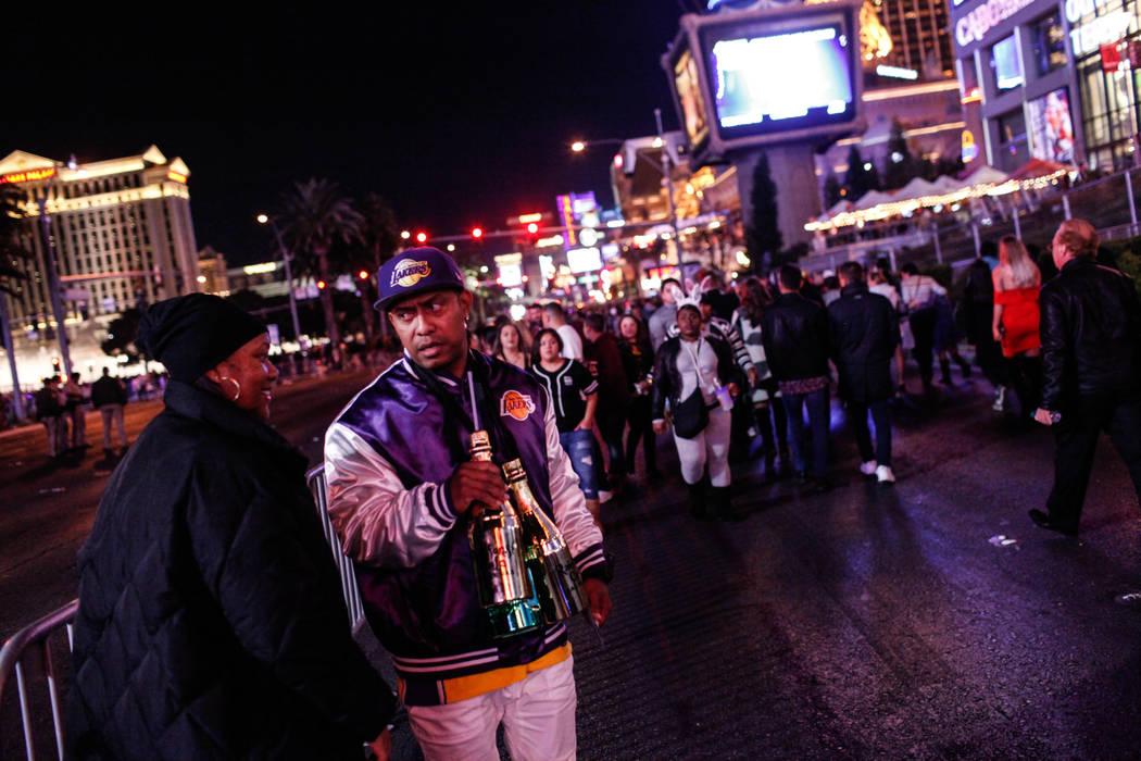 Xiomarra Barton, 46, left, and Juan Barton, 43, right, both of San Diego, take a rest along the Strip on New Year's Eve in Las Vegas, Sunday, Dec. 31, 2017. Joel Angel Juarez Las Vegas Review-Jour ...