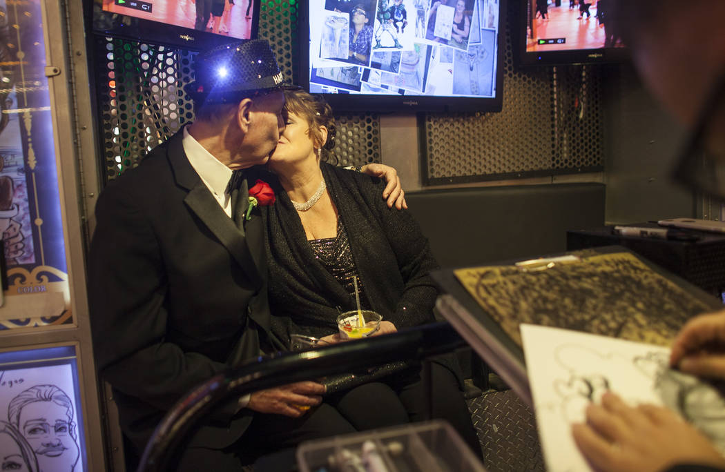 Duke Gressett and his wife Melody Gressett kiss as they have their caricature drawn at the Fremont Street Experience in Las Vegas, Sunday, Dec. 31, 2017, shortly after getting married. Rachel Asto ...