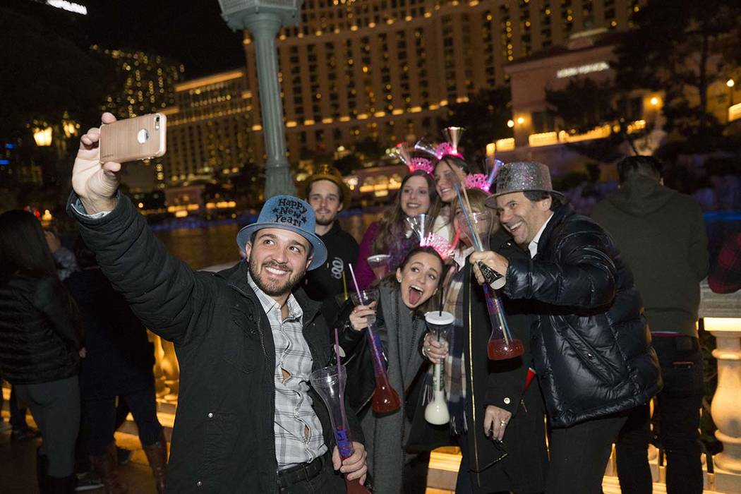 Humberto Carvalho of Brazil takes a selfie with members of his family at the Bellagio fountains on New Year's Eve, Sunday, Dec. 31, 2017. Richard Brian Las Vegas Review-Journal @vegasphotograph