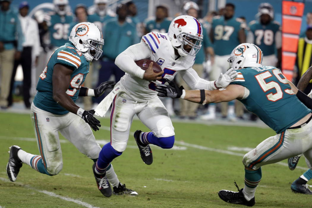 Miami Dolphins outside linebacker Lawrence Timmons (94) and outside linebacker Chase Allen (59) attempt to tackle Buffalo Bills quarterback Tyrod Taylor (5), during the second half of an NFL footb ...