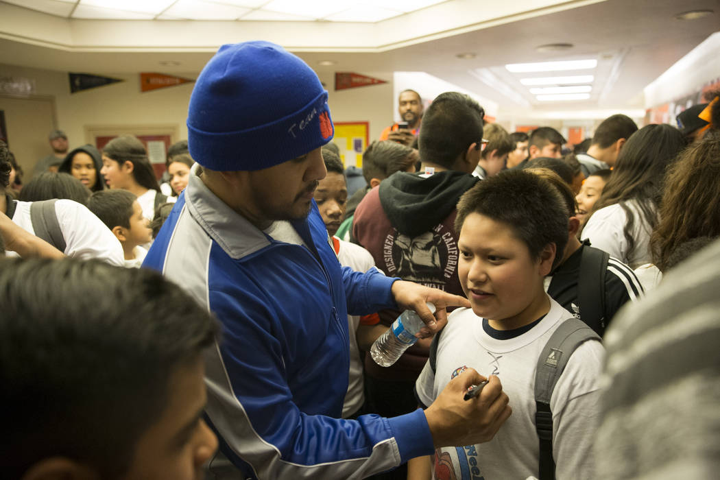 Former professional boxer Fernando Vargas signs the shirt of Jovany Salazar, 11, during a Clark County School District Peace Week assembly at Ed Von Tobel Middle School in Las Vegas, Thursday, Jan ...