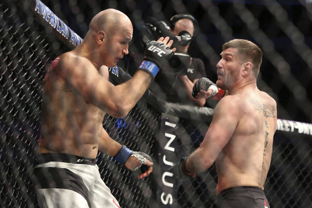Stipe Miocic, right, fights Junior Dos Santos in a mixed martial arts bout at UFC 211 for the UFC heavyweight championship, Saturday, May 13, 2017, in Dallas. Miocic retained his heavyweight title ...