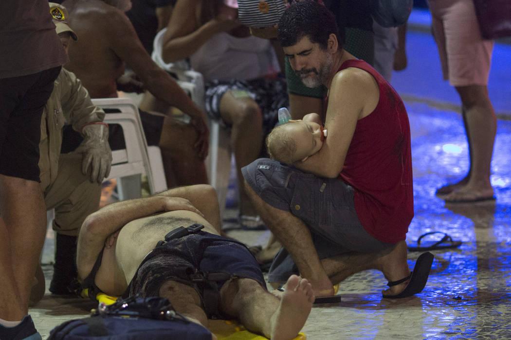 A man holds a baby next to an injured man after a car drove into the crowded seaside boardwalk along Copacabana beach in Rio de Janeiro, Brazil, Thursday, Jan. 18, 2018.  (Silvia Izquierdo/AP)