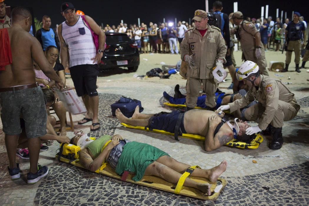 Firefighters give the first aid to people that were hurt after a car drove into the crowded seaside boardwalk along Copacabana beach in Rio de Janeiro, Brazil, Thursday, Jan. 18, 2018. (Silvia Izq ...