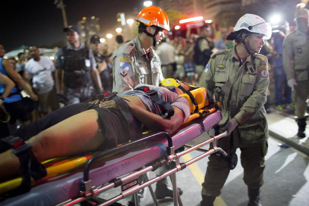 Firefighters carry a woman on a stretcher after a car drove into the crowded seaside boardwalk along Copacabana beach in Rio de Janeiro, Brazil, Thursday, Jan. 18, 2018. (Silvia Izquierdo/AP)