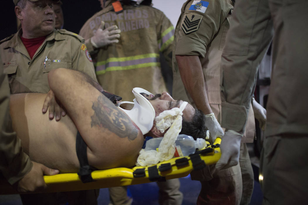 Firefighters carry a man on a stretcher after a car drove into the crowded seaside boardwalk along Copacabana beach in Rio de Janeiro, Brazil, Thursday, Jan. 18, 2018. Military police said on Twit ...
