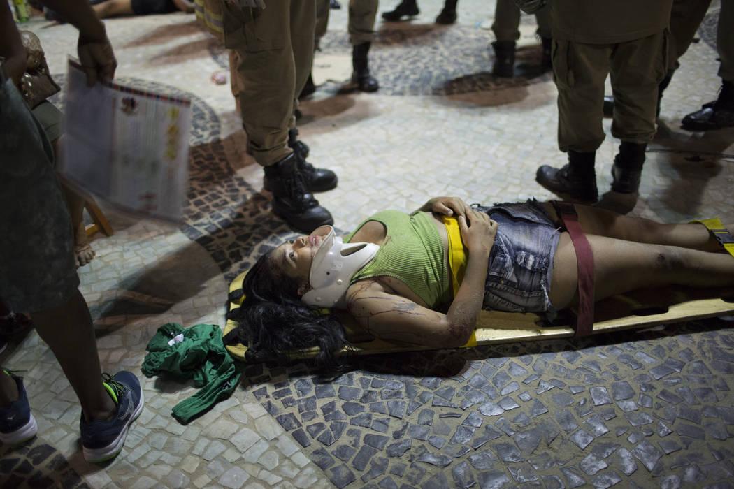 A woman lies on a stretcher waiting for an ambulance after a car drove into the crowded seaside boardwalk along Copacabana beach in Rio de Janeiro, Brazil, Thursday, Jan. 18, 2018. (Silvia Izquier ...