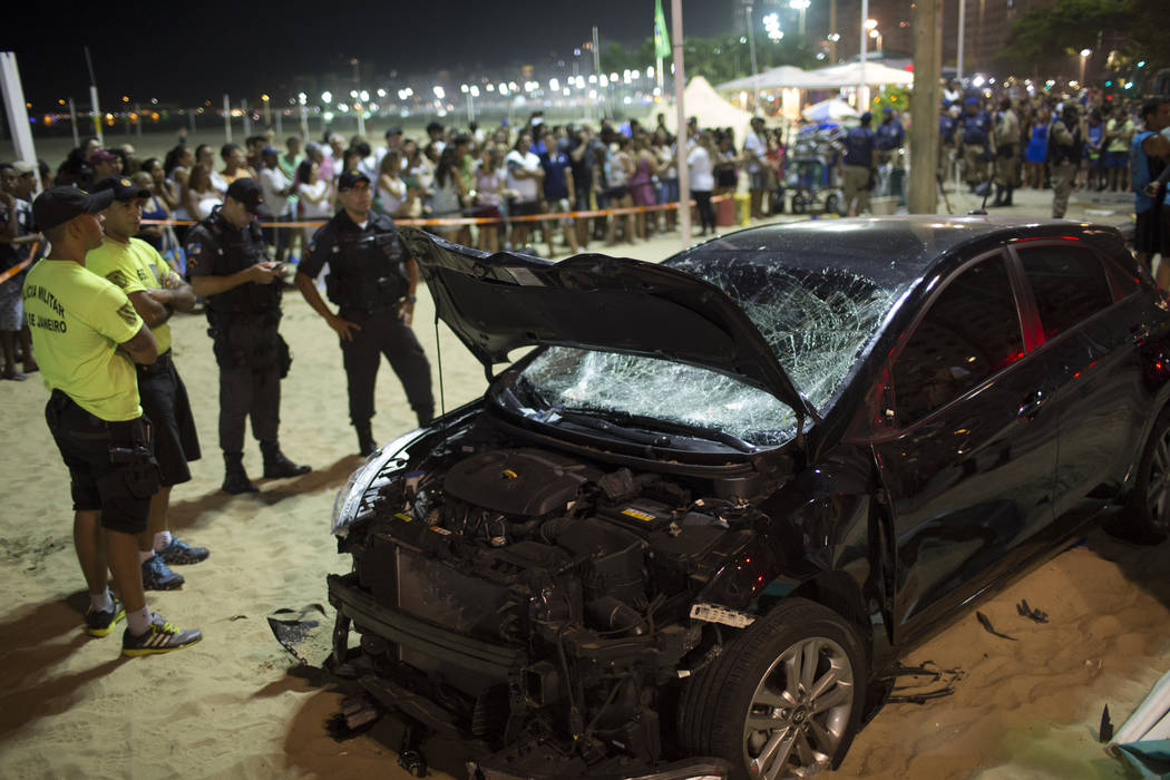 Police officers stand next to the a car that has driven into the crowded seaside boardwalk along Copacabana beach in Rio de Janeiro, Brazil, Thursday, Jan. 18, 2018. (Silvia Izquierdo/AP)