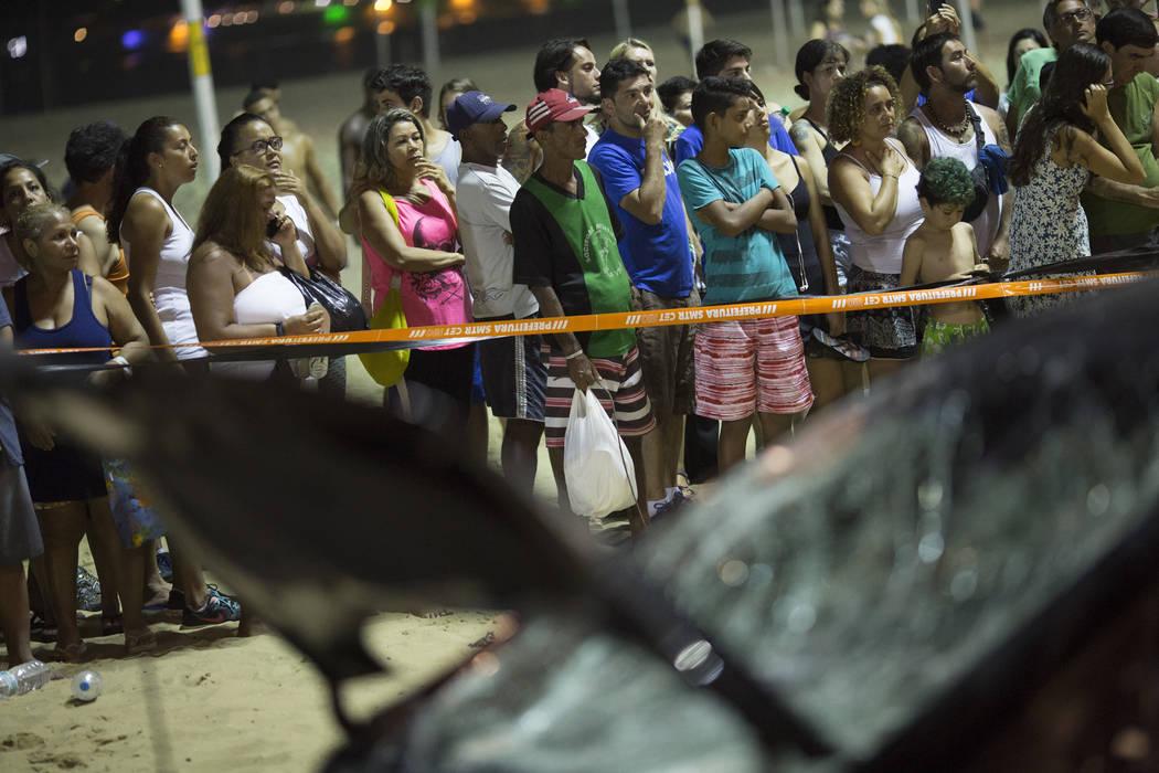 People watch a car that has driven into the crowded seaside boardwalk along Copacabana beach in Rio de Janeiro, Brazil, Thursday, Jan. 18, 2018. (Silvia Izquierdo/AP)