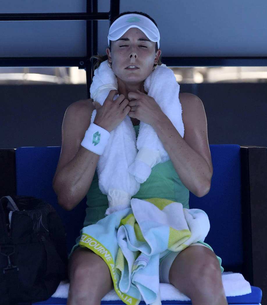 France's Alize Cornet wraps a ice towel around her neck to cool down during her third round match against Belgium's Elise Mertens at the Australian Open tennis championships in Melbourne, Australi ...
