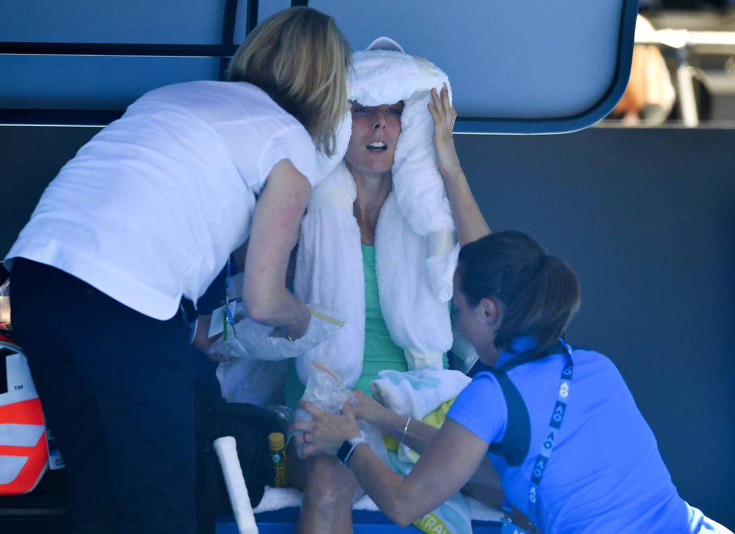 France's Alize Cornet is attended to by a trainer and tournament staff after suffering from the heat during her third round match against Belgium's Elise Mertens at the Australian Open tennis cham ...