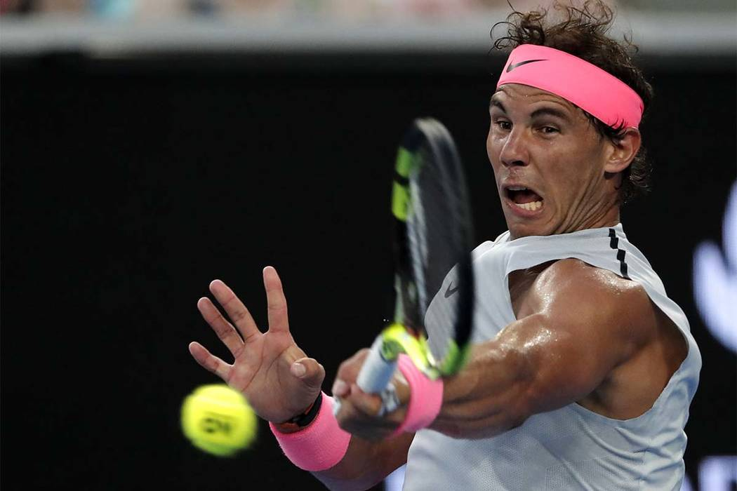 Spain's Rafael Nadal hits a forehand return to Damir Dzumhur of Bosnia and Herzegovina during their third round match at the Australian Open tennis championships in Melbourne, Australia, Friday, J ...
