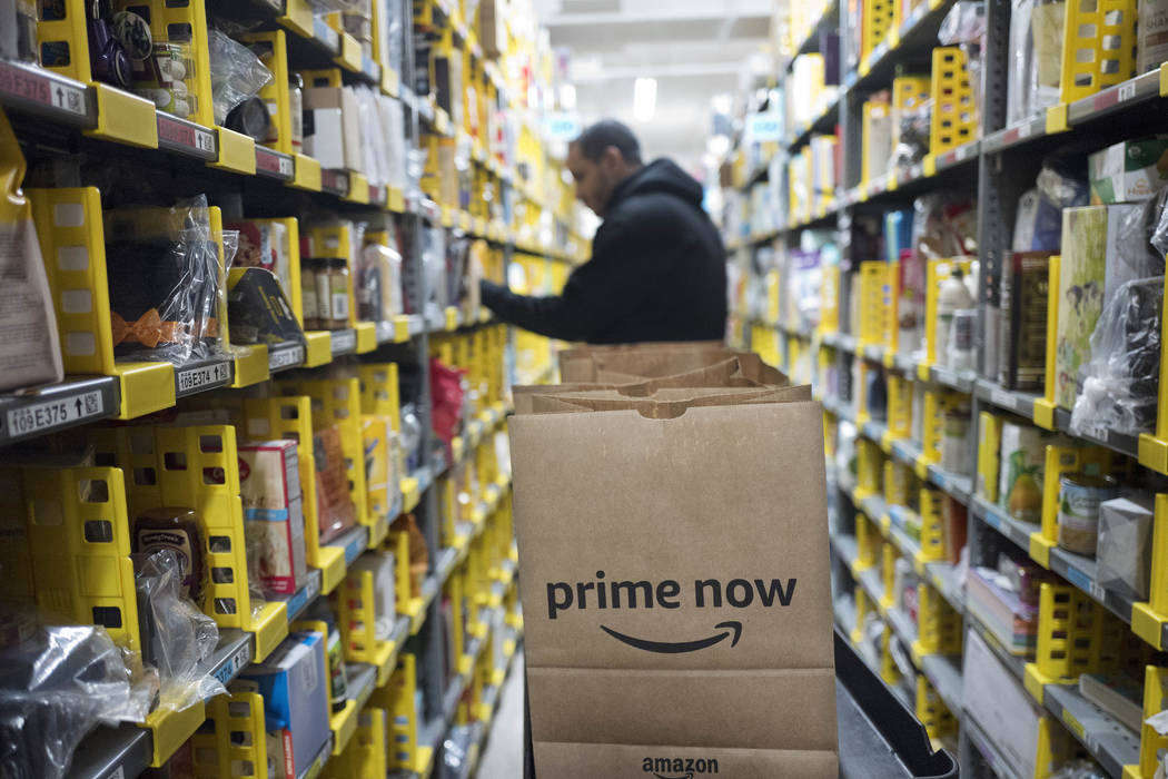 A clerk reaches to a shelf to pick an item for a customer order at the Amazon Prime warehouse, in New York on Dec. 20, 2017. (AP Photo/Mark Lennihan, File)