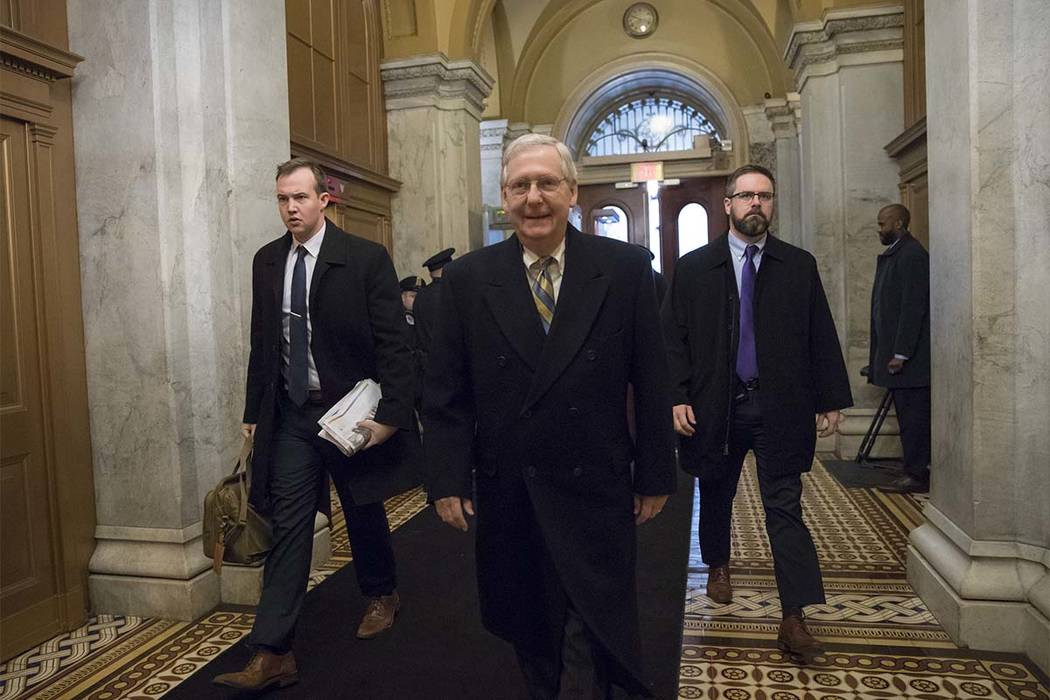 Senate Majority Leader Mitch McConnell, R-Ky., arrives at the Capitol in Washington, Friday, Jan. 19, 2018, as a bitterly-divided Congress hurtles toward a government shutdown this weekend in a pa ...