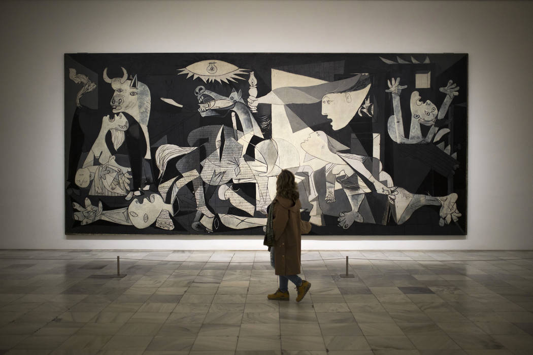 A woman looks at the Guernica painting by Spanish artist Pablo Picasso during an exhibition at the Reina Sofia museum in Madrid, Monday, April 3, 2017.  (AP Photo/Francisco Seco)