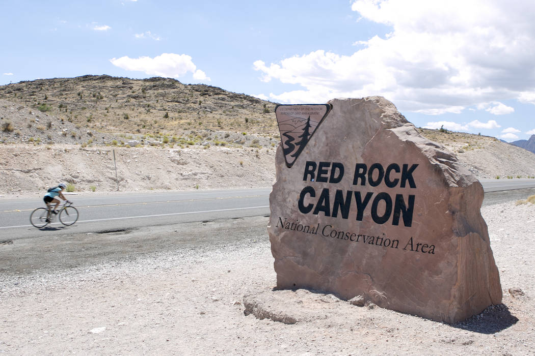 A biker passes a sign for Red Rock Canyon National Conservation Area on Tuesday, Aug. 22, 2017, in Las Vegas. (Las Vegas Review-Journal)