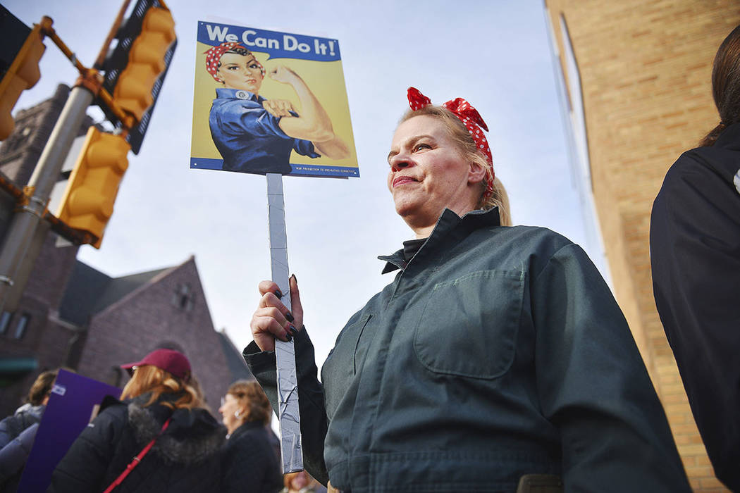 """Sheila Dathe wears a """"Rosie the Riveter"""" inspired work uniform to the Women's March Saturday, Jan. 20, 2018 in downtown   Sioux Falls, S.D.  The march is among dozens of rallies  ..."""