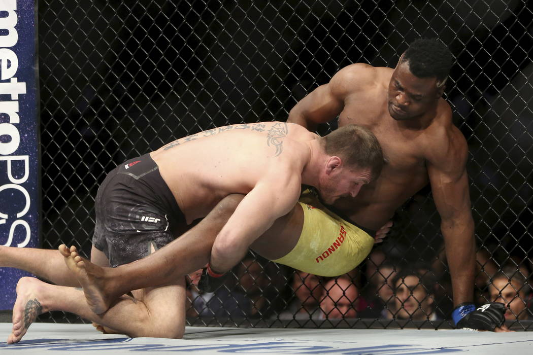 Stipe Miocic, left, takes down Francis Ngannou during a heavyweight championship mixed martial arts bout at UFC 220, early Sunday, Jan. 21, 2018, in Boston. Miocic retained his title via unanimous ...