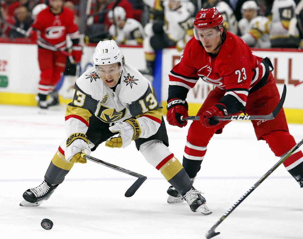 Golden Knights' Brendan Leipsic (13) and Carolina Hurricanes' Brock McGinn (23) eye the puck during the first period of an NHL hockey game, Sunday, Jan. 21, 2018, in Raleigh, N.C. (AP Photo/Karl B ...