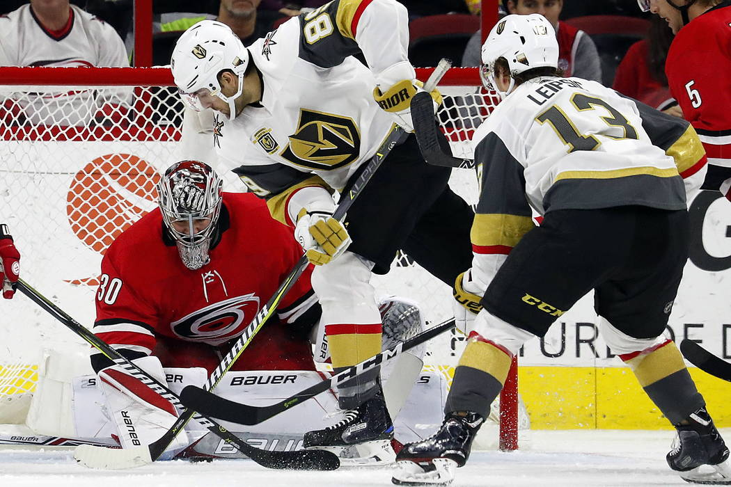 Carolina Hurricanes goaltender Cam Ward (30) tries to freeze the puck as he battles Vegas Golden Knights' Alex Tuch (89) with Golden Knights' Brendan Leipsic (13) looking on during the second peri ...