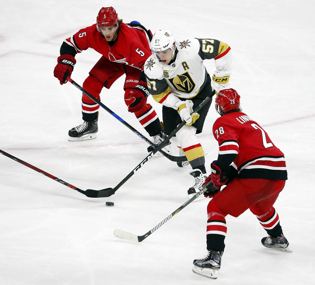 Vegas Golden Knights' David Perron (57) drives the puck between Carolina Hurricanes' Noah Hanifin (5) and Elias Lindholm (28) during the third period of an NHL hockey game, Sunday, Jan. 21, 2018,  ...