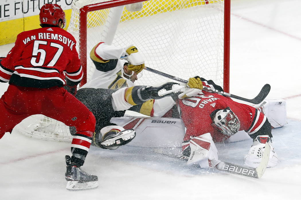 Vegas Golden Knights' William Carrier (28) collides with Carolina Hurricanes goaltender Cam Ward (30) with Hurricanes' Trevor van Riemsdyk (57) nearby during the third period of an NHL hockey game ...