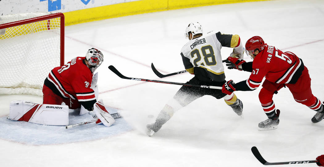 Vegas Golden Knights' William Carrier (28) skates past Carolina Hurricanes' Trevor van Riemsdyk (57) to challenge goaltender Cam Ward (30) during the third period of an NHL hockey game, Sunday, Ja ...