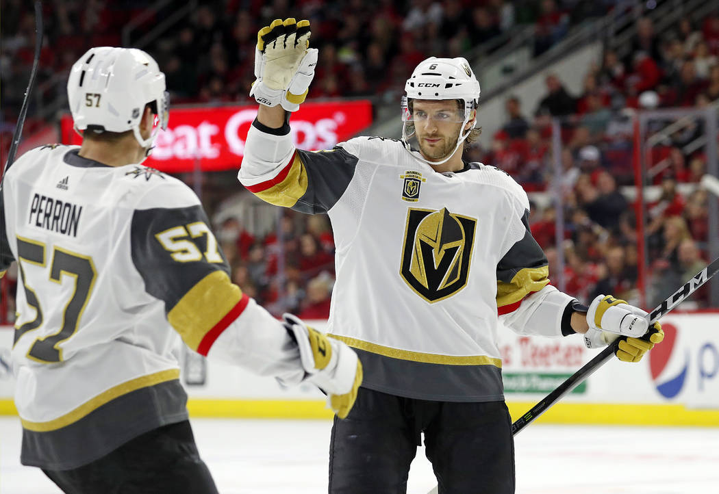Golden Knights' Colin Miller (6) celebrates his goal against the Carolina Hurricanes with teammate David Perron (57) during the first period of an NHL hockey game, Sunday, Jan. 21, 2018, in Raleig ...
