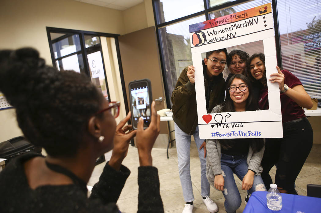 Denise Hooks, outreach and engagement coordinator for Women's March, left, takes a photo of Valley High School students, clockwise from left, Kai Catarata, Alessandra Quintanilla, Fatima Loumrhari ...