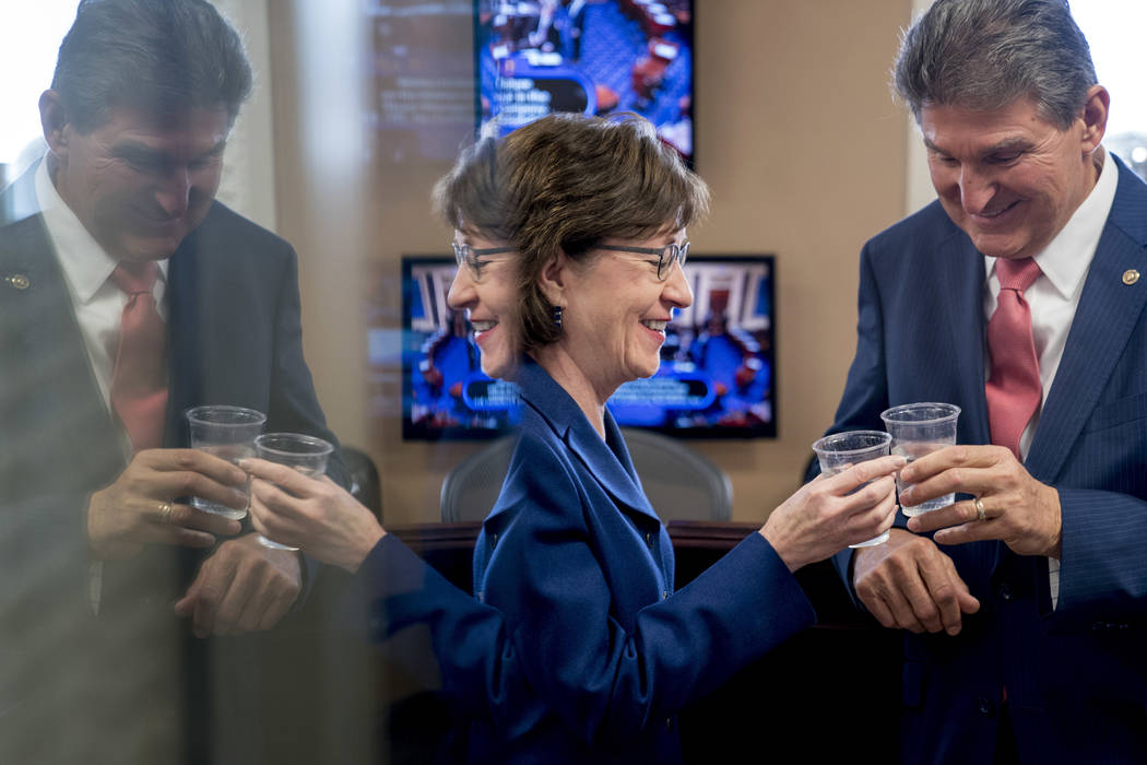 Sen. Susan Collins, R-Maine, left, and Sen. Joe Manchin, D-W.Va., right, clink glasses in a toast to each other as they wait to speak at a news conference on Capitol Hill in Washington, Monday, Ja ...