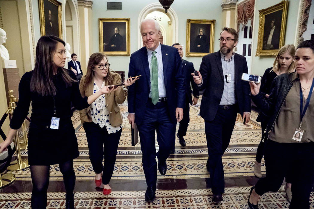 Senate Majority Whip Sen. John Cornyn, R-Texas, speaks to reporters as he walks to the Senate Chamber at the Capitol in Washington, Monday, Jan. 22, 2018, after the Senate reached an agreement to  ...