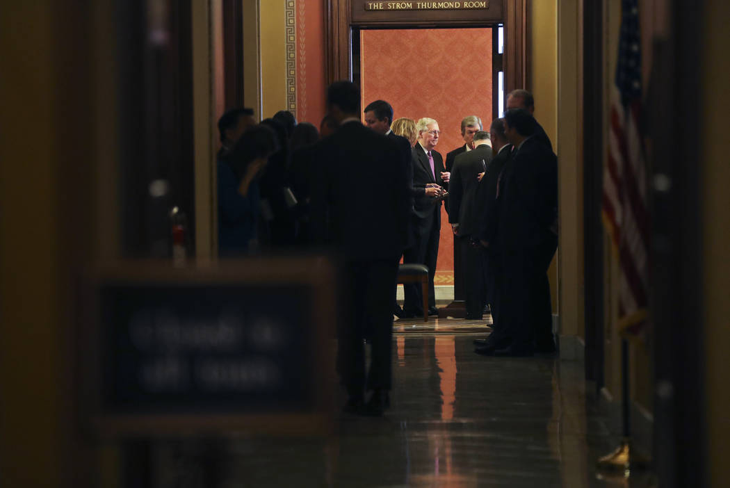Senate Majority Leader Mitch McConnell of Ky., center, and Sen. Roy Blunt, R-Mo., at the end of a close-door meeting with fellow Republican senators, Monday, Jan. 22, 2018, on Capitol Hill in Wash ...