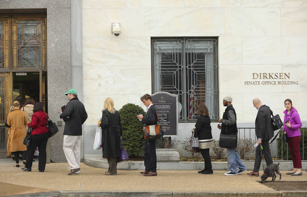 People wait in line at Dirksen Senate Office building at one of the few entrances opened for staff members at the U.S. Capitol in Washington as Day Three of the government shutdown continues on Mo ...