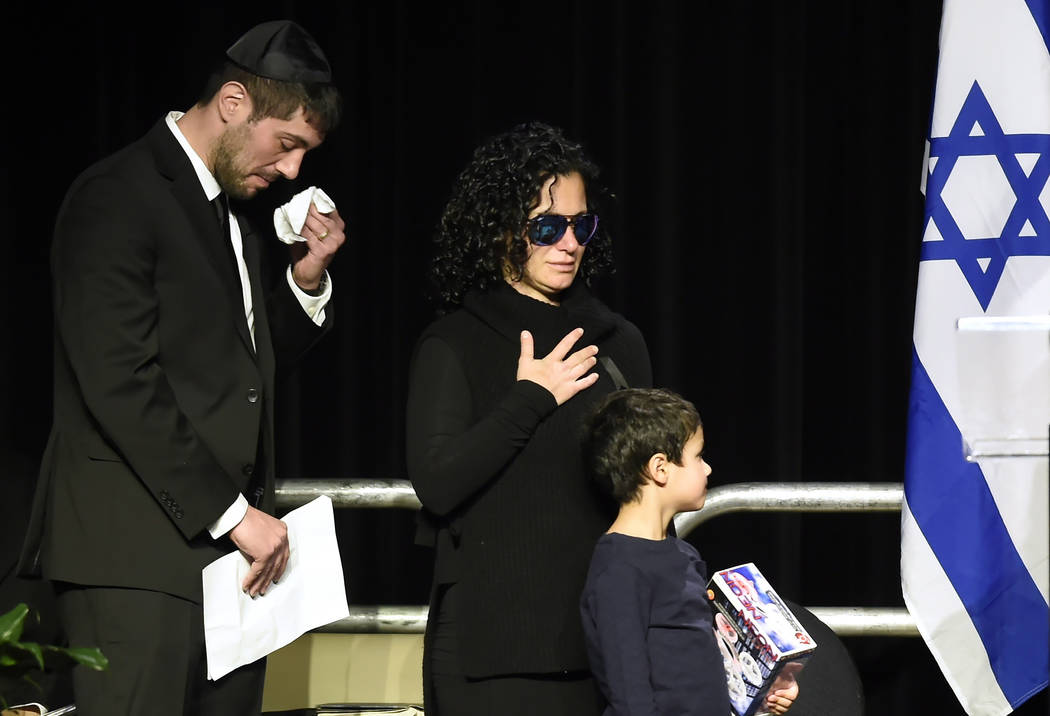 FILE - In this Dec. 21, 2017 file photo, Jonathon Sherman wipes his tears as he and his sister Lauren walk to the stage during a memorial service in Mississauga, Ontario, for their parents Barry a ...