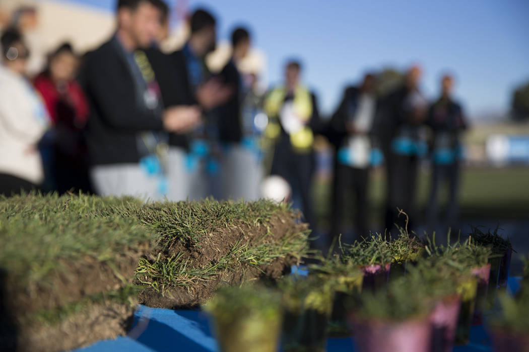 People attend a Las Vegas Lights FC event to lay the first pieces of turf at Cashman Field to help transition the stadium from a baseball to a soccer venue, in Las Vegas, Wednesday, Jan. 24, 2018. ...