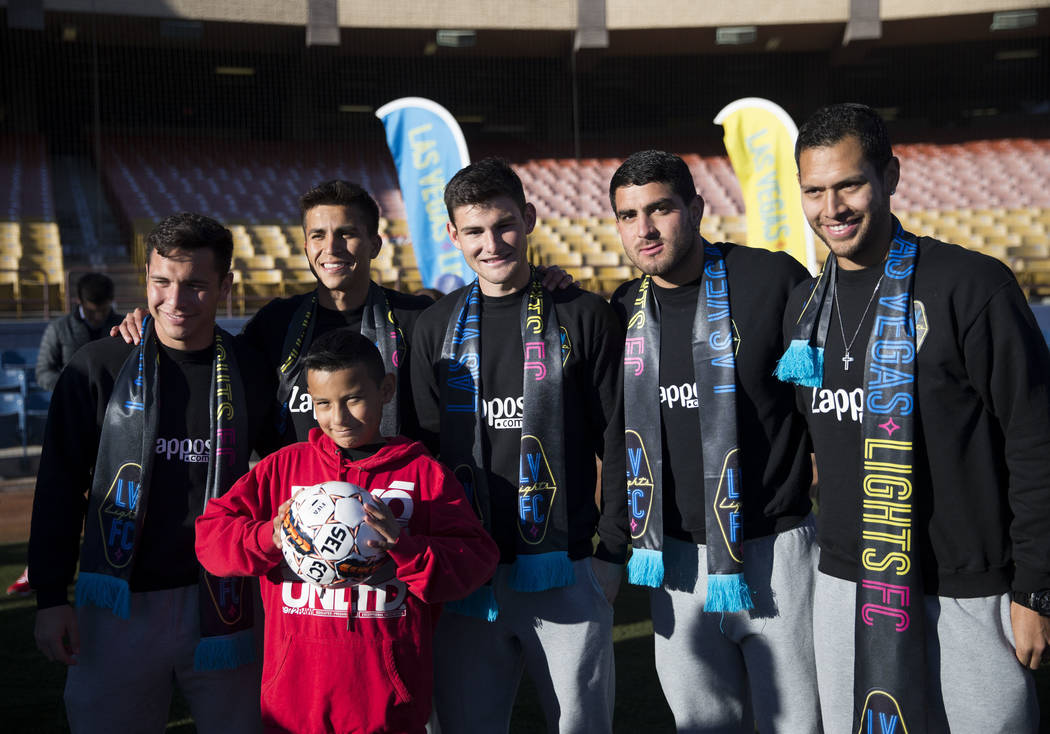 Gio Cana, 10, of Las Vegas, is photographed with players of the Las Vegas Lights FC from left, Julian Portugal, Adolfo Guzman, Matt Thomas, Marco Cesar Jaime, and Sebastian Hernandez, during an ev ...
