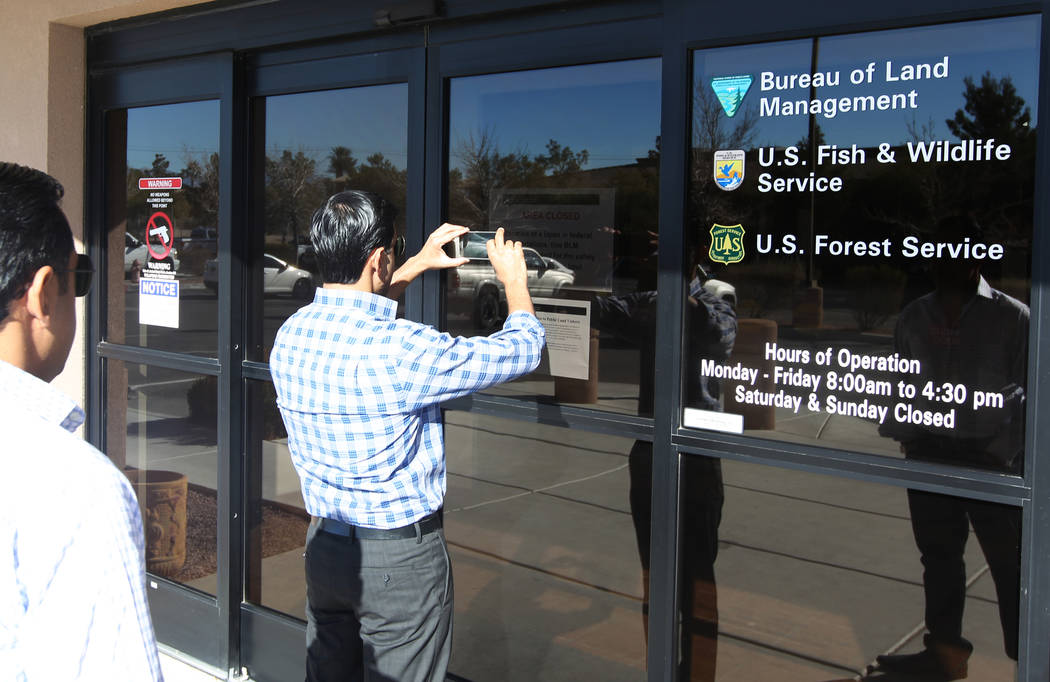 Umer Malik takes a photo of a closed sign at a U.S. Government office building at 4701 N. Torrey Pines Drive in Las Vegas Monday, Jan. 22, 2018. Malik and his brother Imran Malik, left, were at th ...
