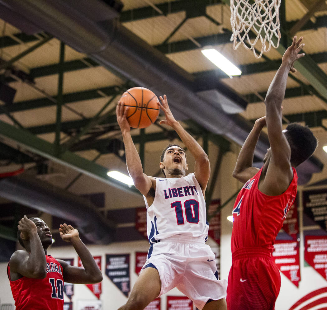Liberty's Jordan Holt (10) goes up for a shot while Coronado's Taieem Comeaux (44) tries to block him and Tyrelle Hunt (10) watches at Liberty High School on Tuesday, Jan. 23, 2018. Liberty won 98 ...