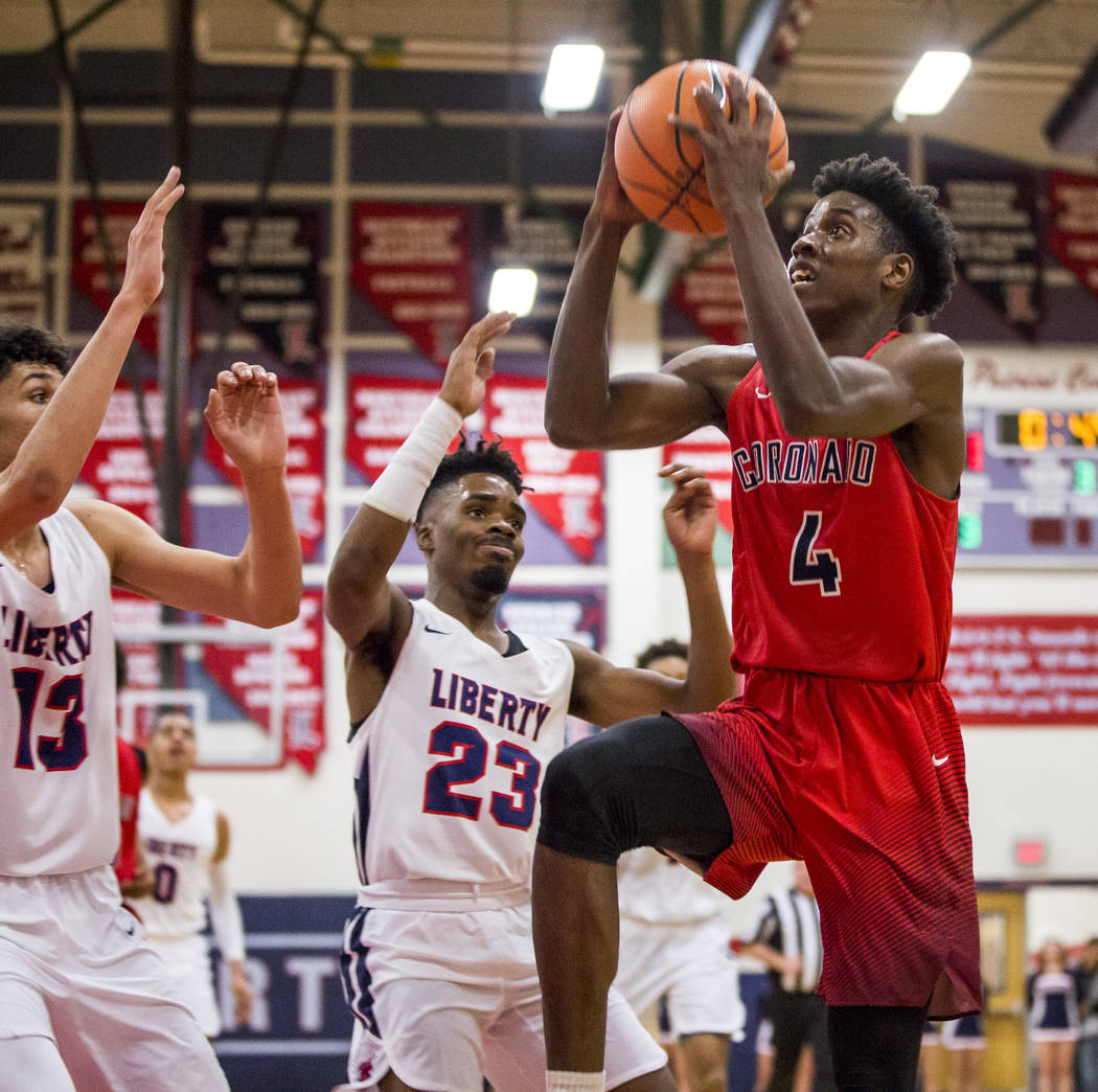 Coronado's Tahj Comeaux (4) goes up for a shot while Liberty's Davion Ware (23) and Terrance Marigney (13) watch the action at Liberty High School on Tuesday, Jan. 23, 2018. Liberty won 98-87.  Pa ...