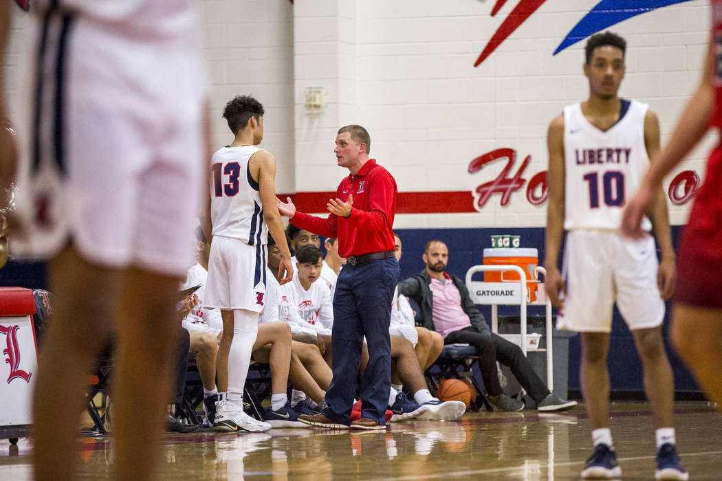 Liberty head coach Stefan Berg talks to Terrance Marigney (13) in between plays during a game against Coronado at Liberty High School on Tuesday, Jan. 23, 2018. Liberty won 98-87.  Patrick Connoll ...