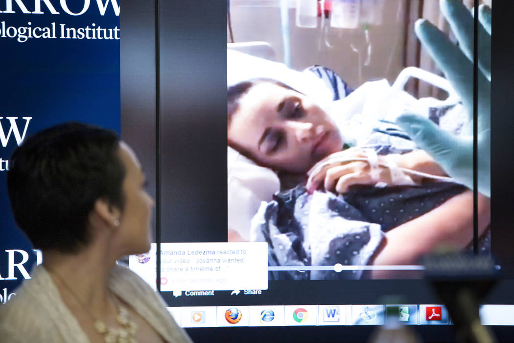 Route 91 Harvest festival shooting survivor Jovanna Calzadillas of San Tan Valley, Ariz. watches a video clip of herself in a hospital bed during a press conference on her recovery at the Barrow N ...